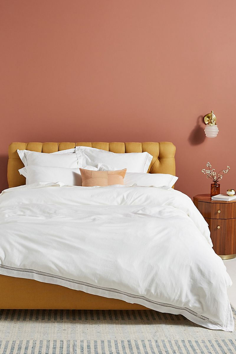 Comfy bedroom featuring earthy pink walls and a mustard bed