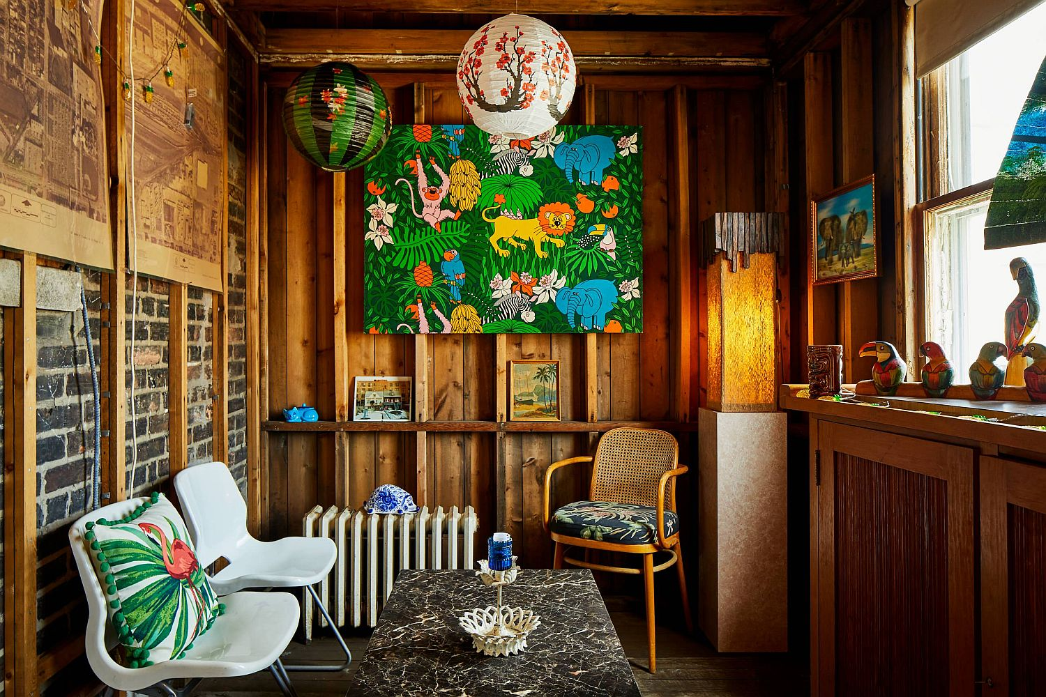 Cozy-small-tropical-living-room-of-Chicago-home-with-woodsy-wall-and-colorful-wall-art