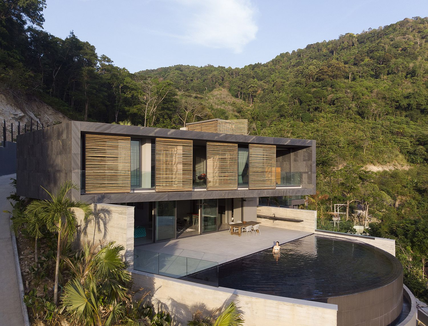 Curved pool, fabulous bamboo screens and amazing views on sunset in the Andaman Sea shape this Thai home