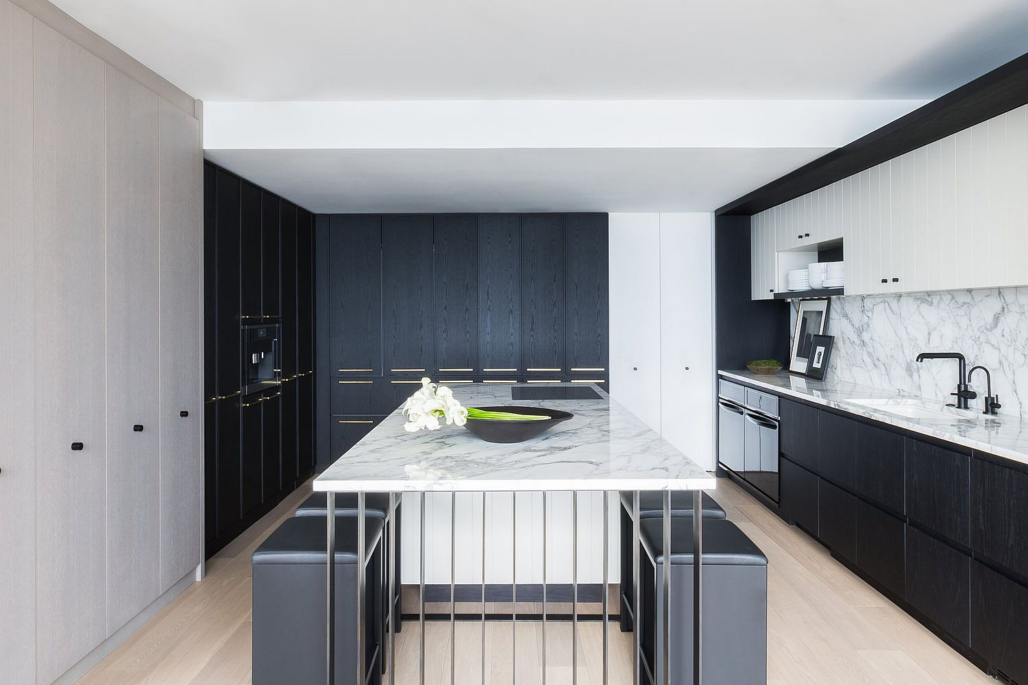 Dark cabinets and marble countertops fashion a kitchen that is elegant and exclusive