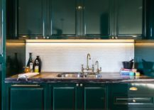 Deep-dark-green-cabinets-coupled-with-shiny-penny-tile-backsplash-in-the-kitchen-217x155