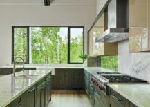 Eat-in-kitchen-with-dark-green-cabinets-and-white-marble-backsplash-is-flooded-with-natural-light-217x155