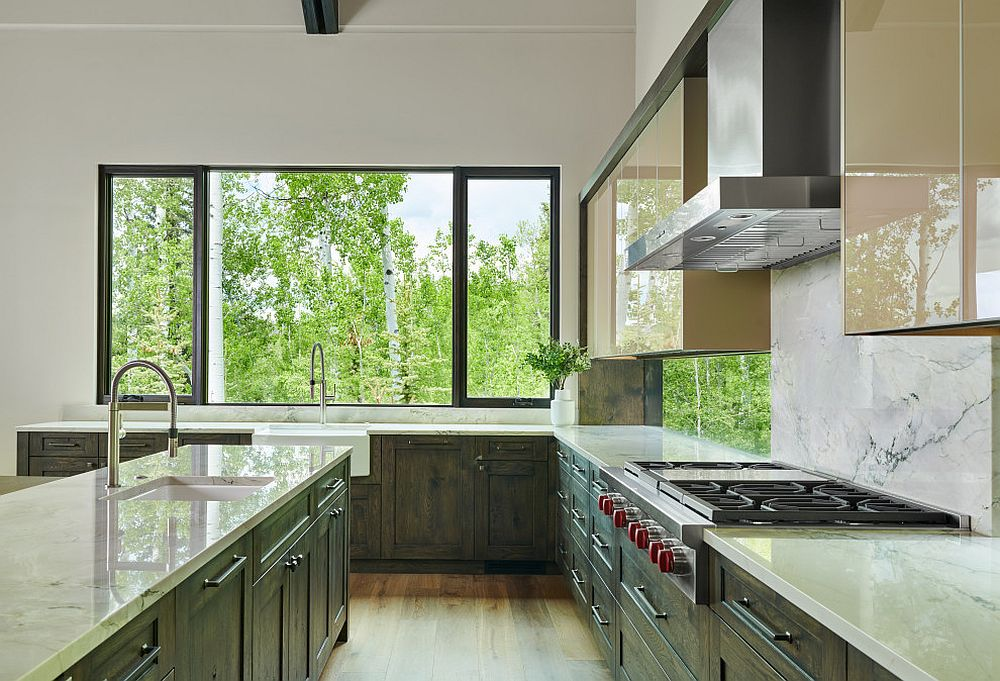 Eat-in-kitchen with dark green cabinets and white marble backsplash is flooded with natural light