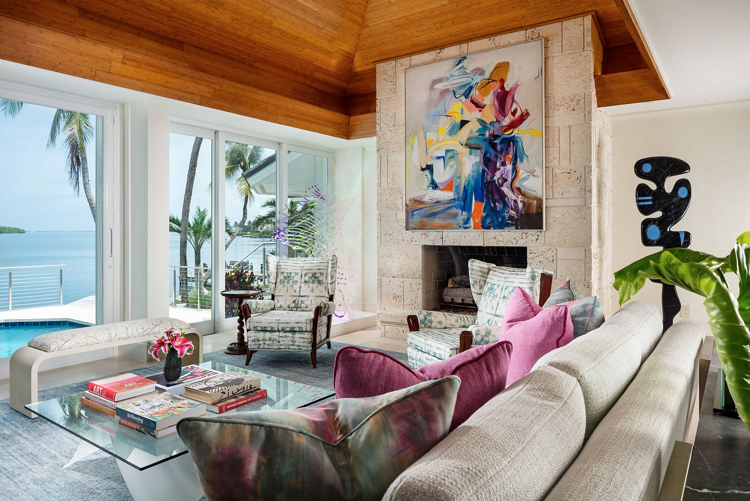 Fireplace-with-colorful-wall-art-sits-at-the-heart-of-the-breezy-tropical-living-room-of-Miami-Home