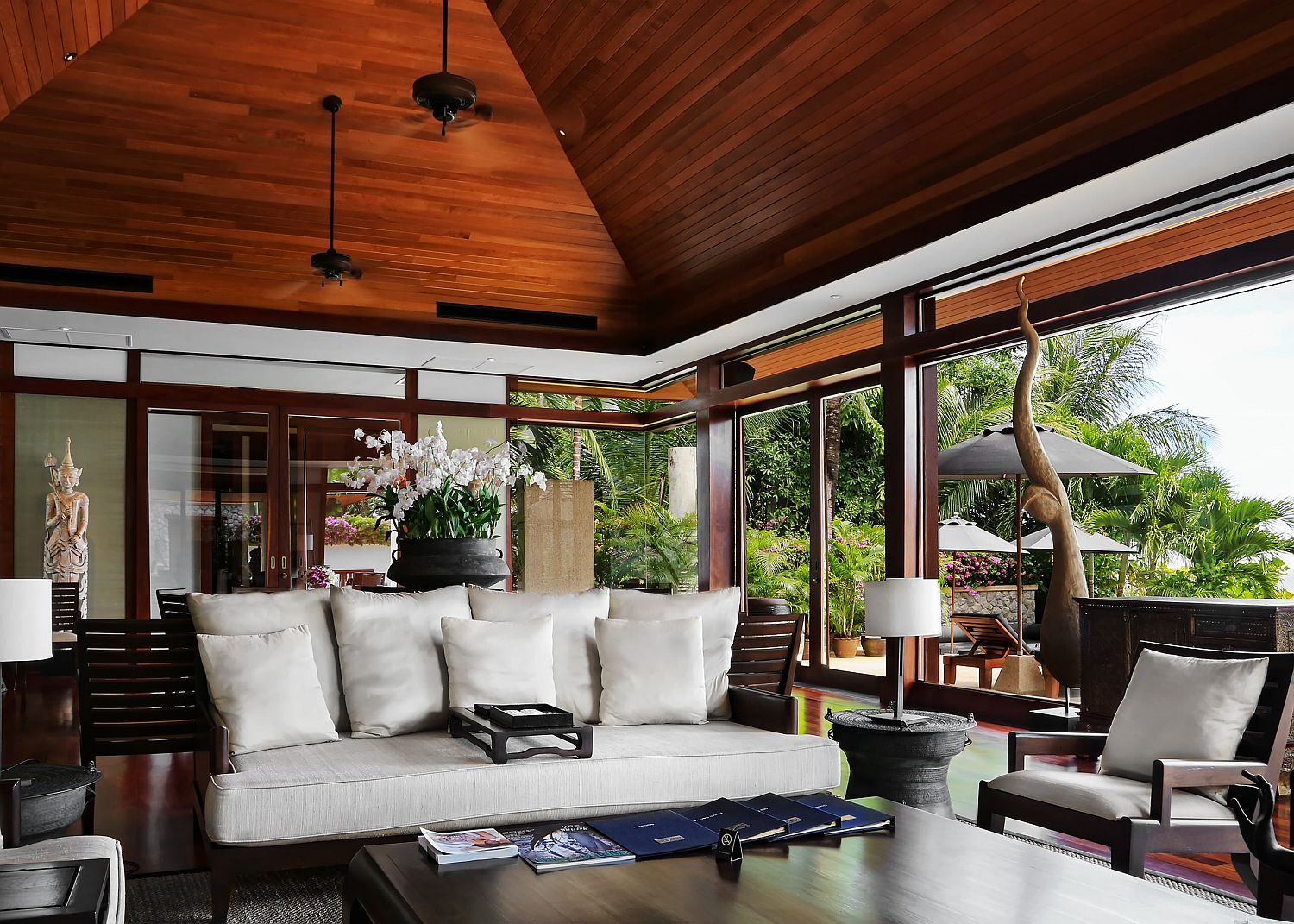 High ceiling in wood aling with ample natural light for the spacious tropical living room