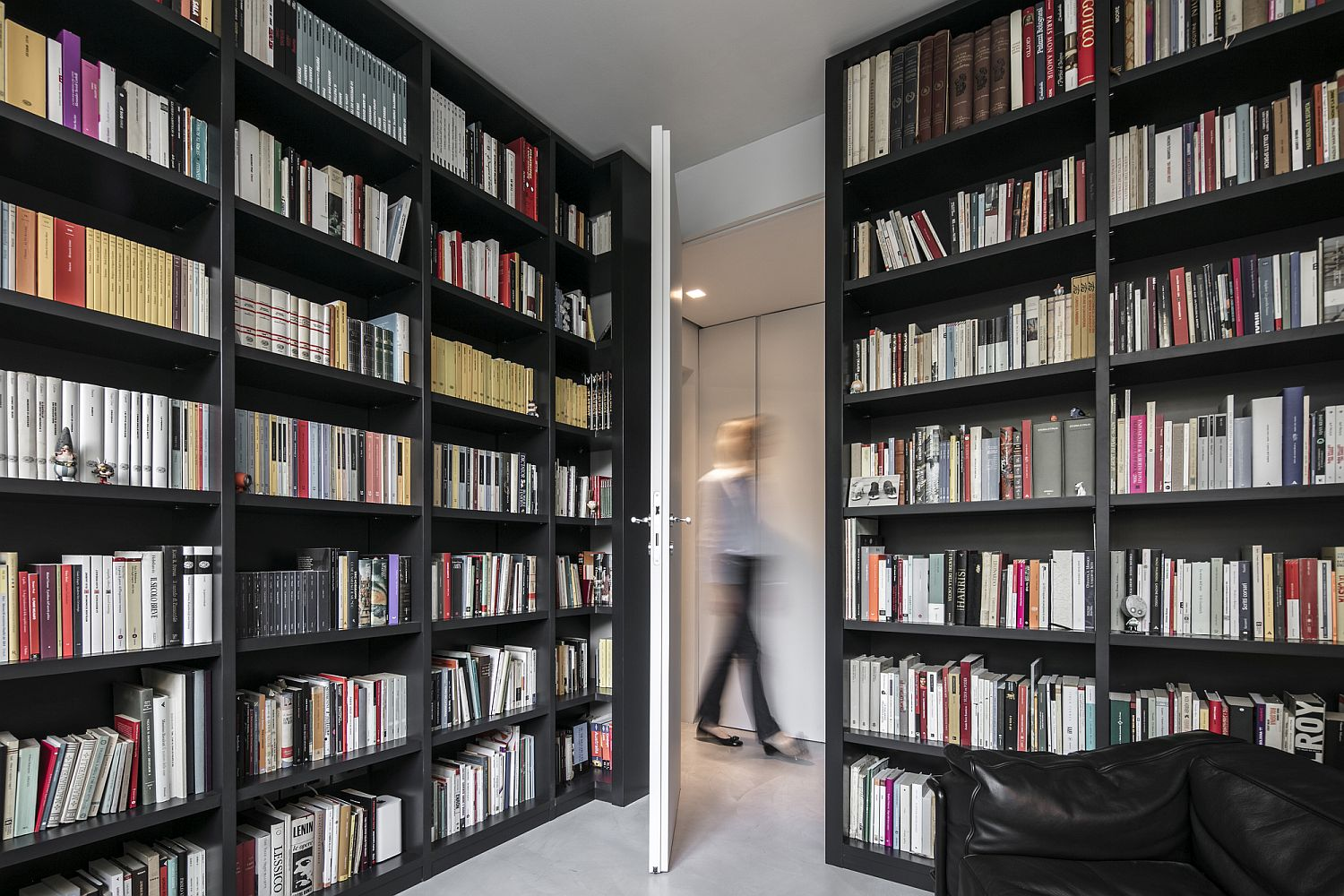 Home library with wall shelves all around that offer plenty of storage space