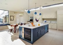 Kitchen-in-white-with-blue-island-that-features-wine-storage-space-blue-pendants-and-skylights-217x155