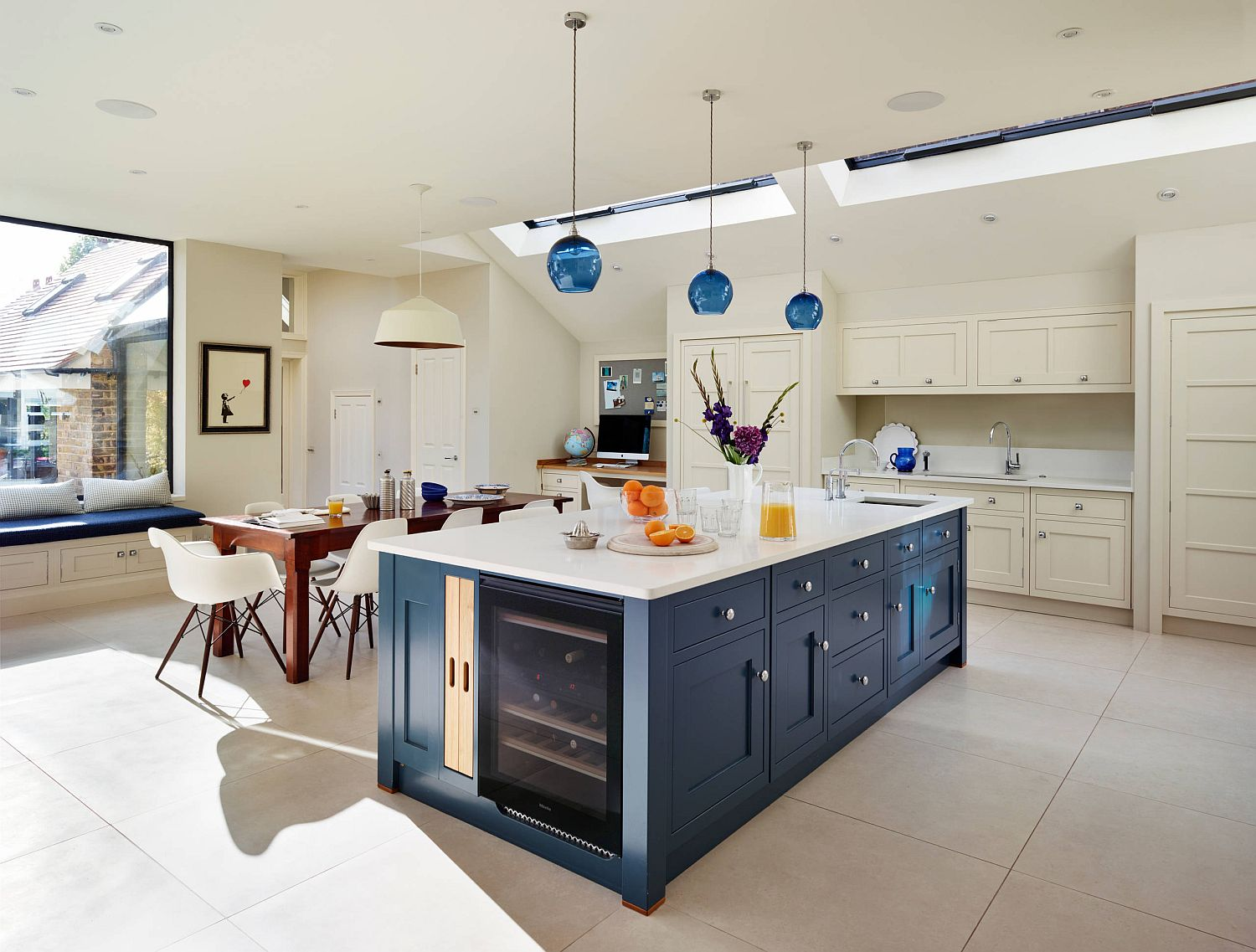 Kitchen-in-white-with-blue-island-that-features-wine-storage-space-blue-pendants-and-skylights