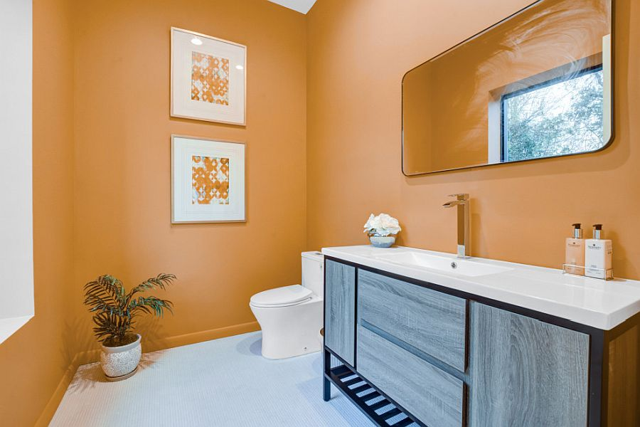 Orange also gives the spacious bathroom a comfy, modern vibe