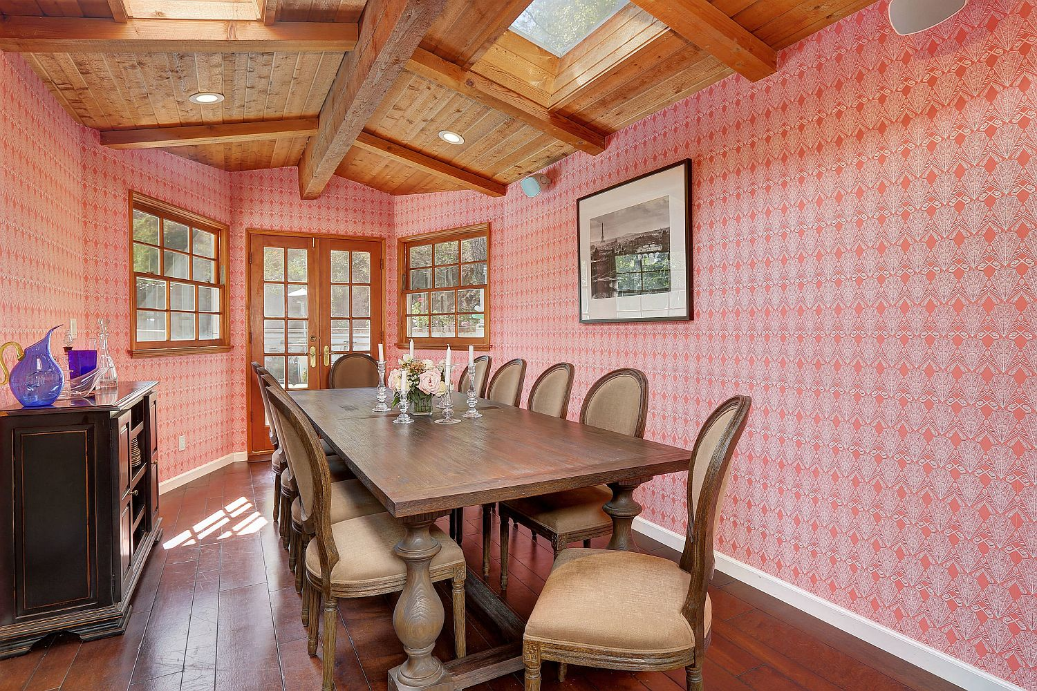 Pink wallpaper covers the walls of this eclectic modern dining room with wooden ceiling