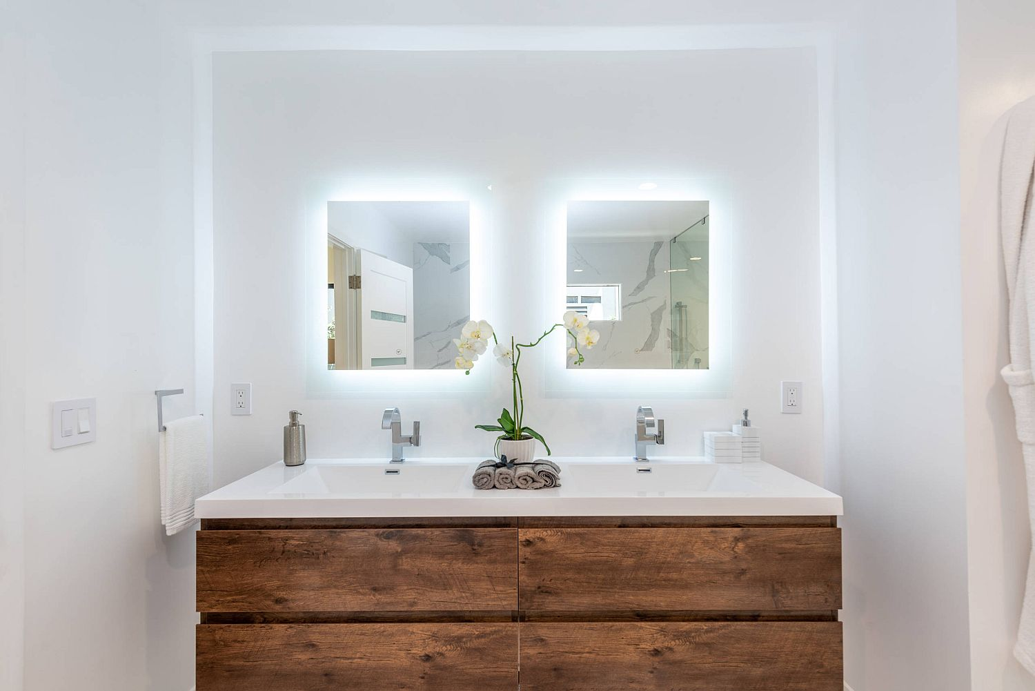 Small wood and white bathroom with a breezy double vanity and lovely lighting that gives it a radiant look