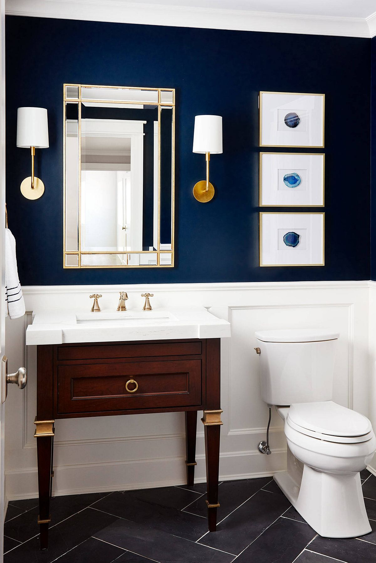 Sophisticated bathroom in dark blue and white with smart art pieces that reflect its style