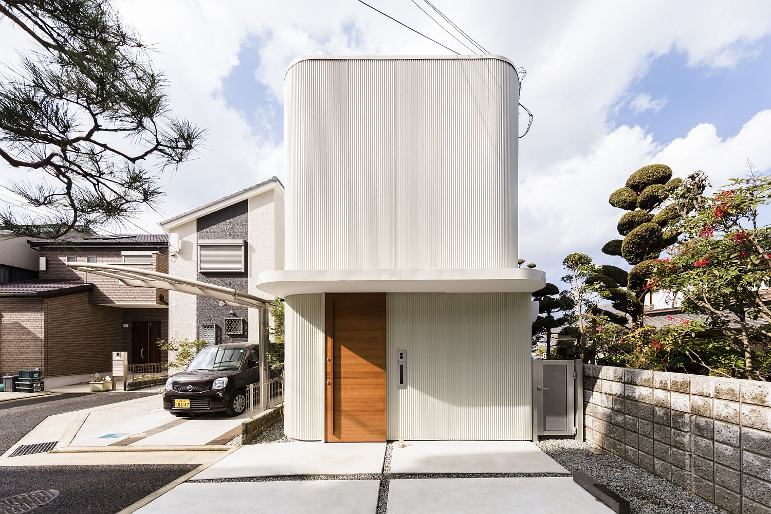 Street facade in white wth curved walls and a wooden entrance door of home in Japan