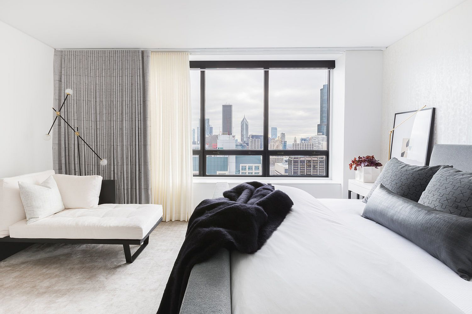 White and gray contemporary bedroom filled with ample natural light