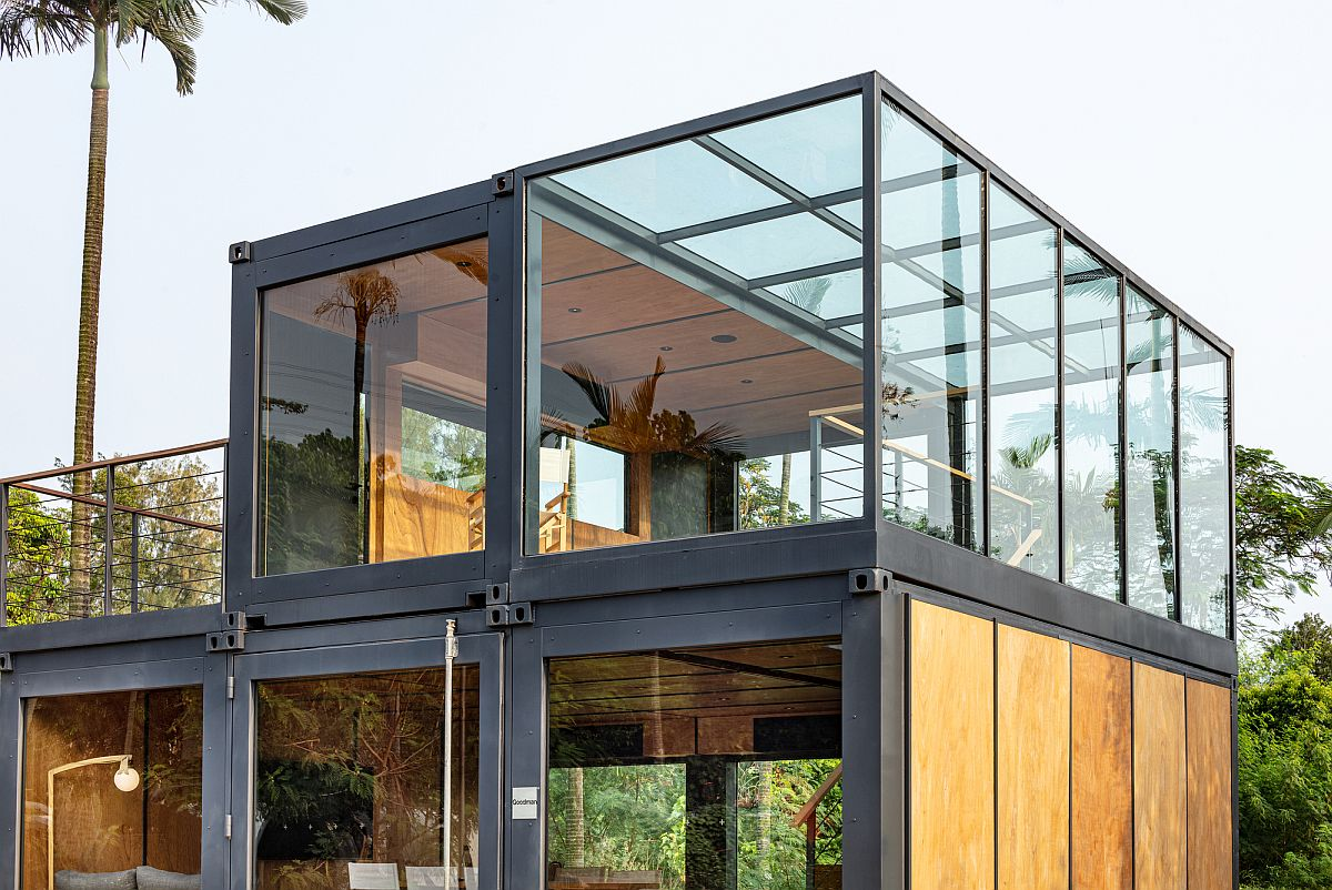 Wood and glass soften the visual impact of the steel frame brought in by the shipping container units