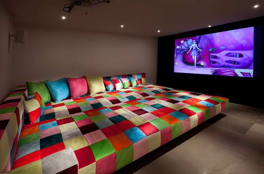 Awesome home theater with seating covered in multi-colored cloth feels unique