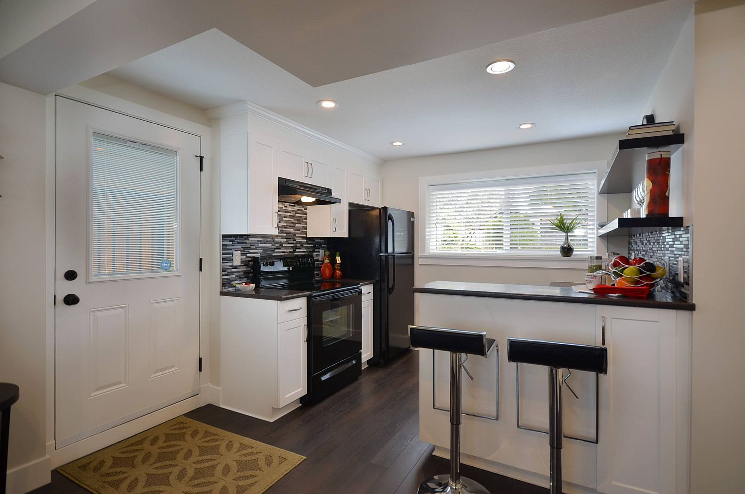 Basement apartment kitchen in white where black appliances stand out even more visually