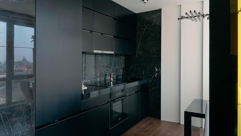 Black cabinets, backsplash and appliances create monochromatic single-wall kitchen