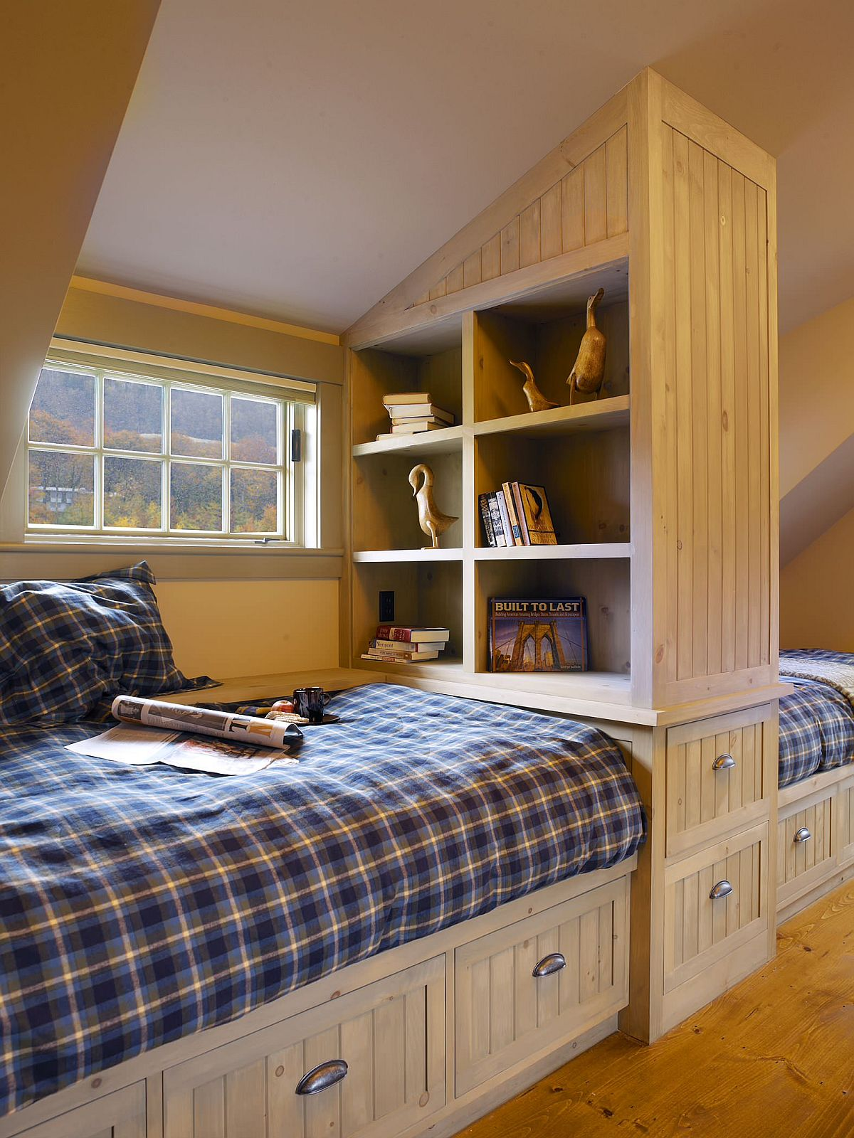 Custom space-savvy attic bedroom design with wooden cabinets and ample storage space