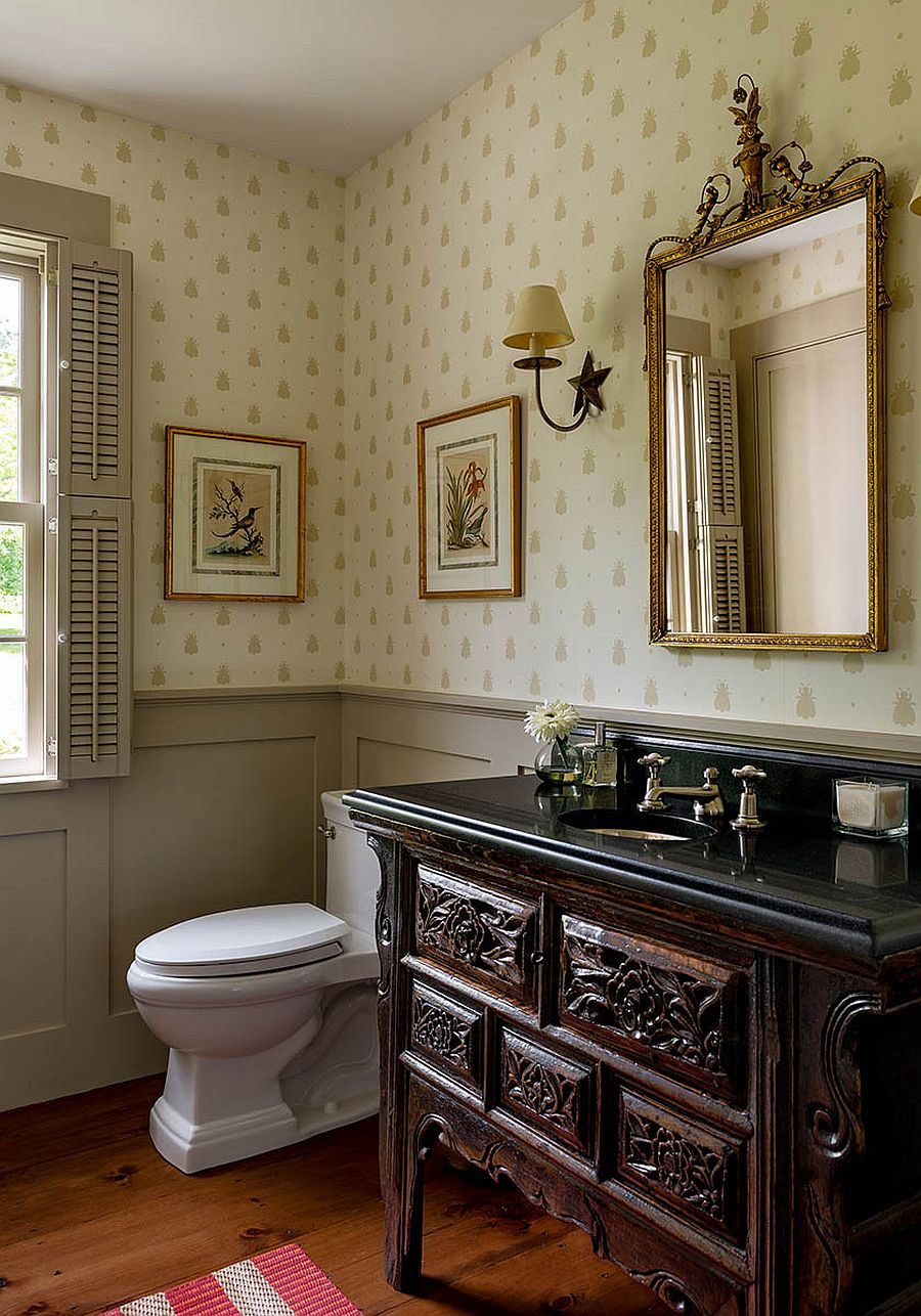 Custom wooden vanity and walls draped in beautiful wallpaper for the spacious farmhouse style powder room