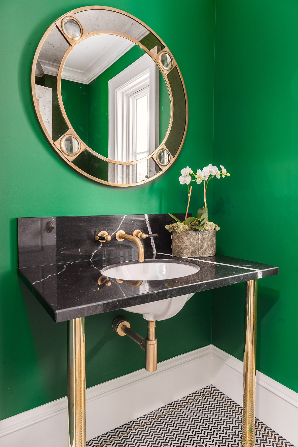 Dark green powder room with gold and black sink and matching mirror frame