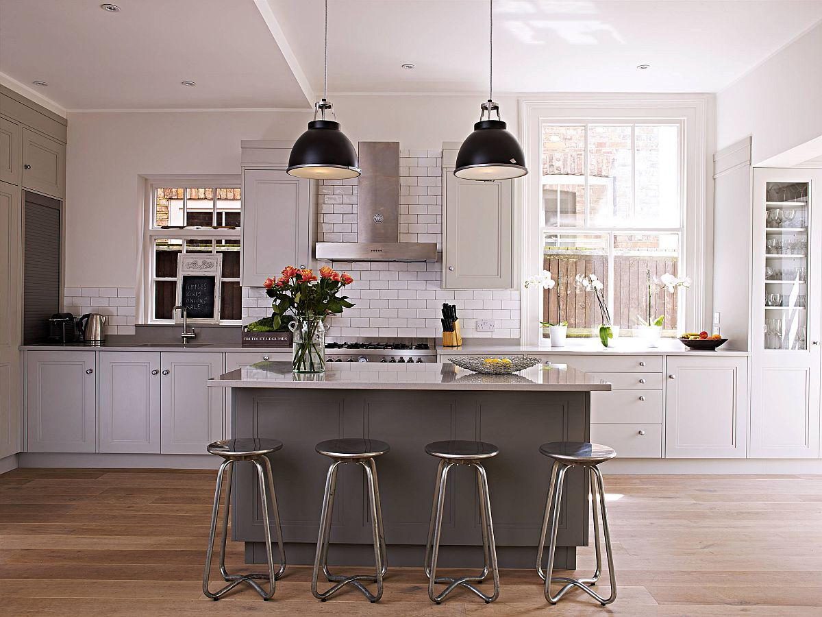 Dark pendants add contrast to the kitchen while the wooden floors provide visual warmth
