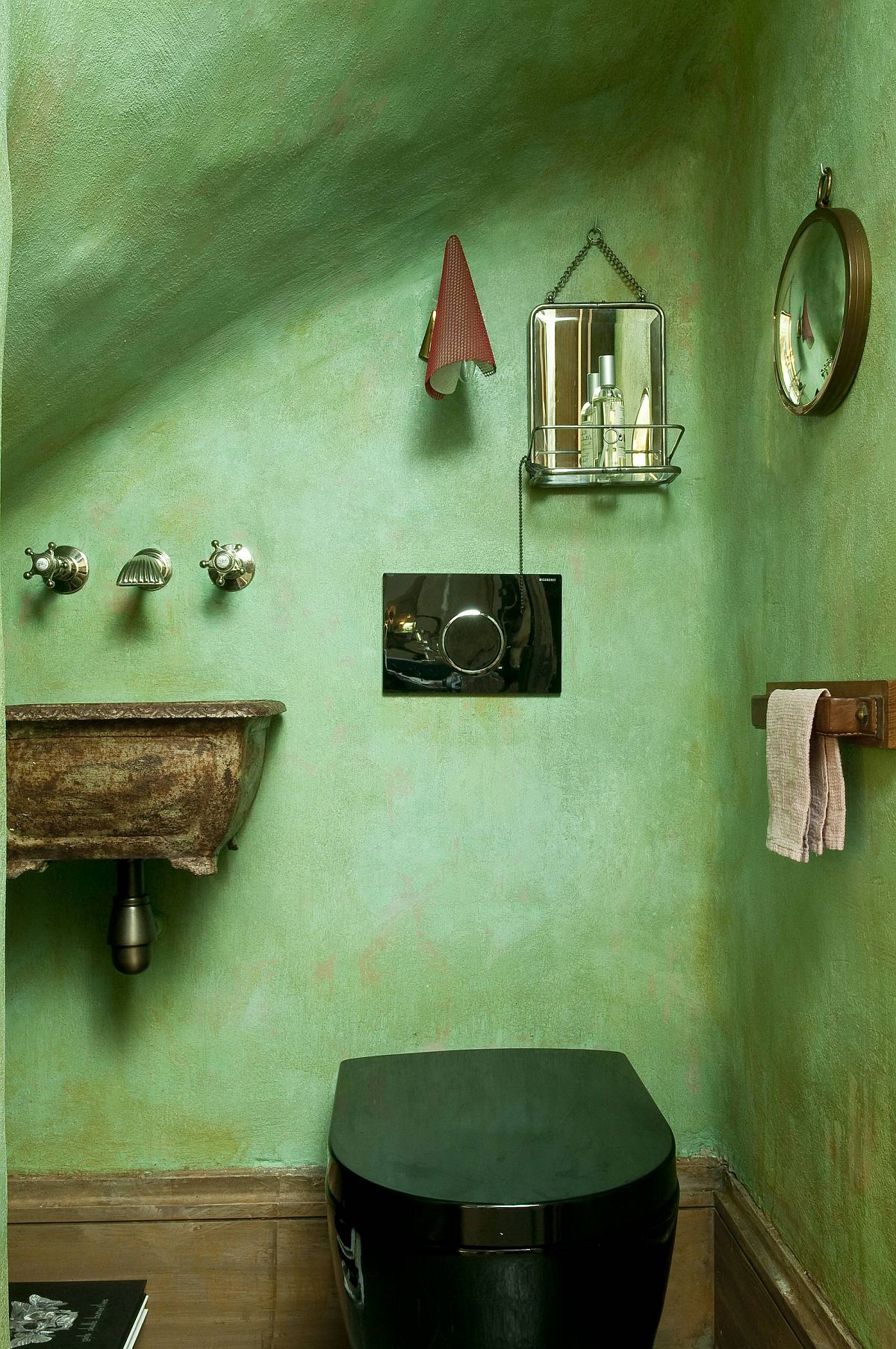 Eclectic powder room of the Paris home with textured walls in green