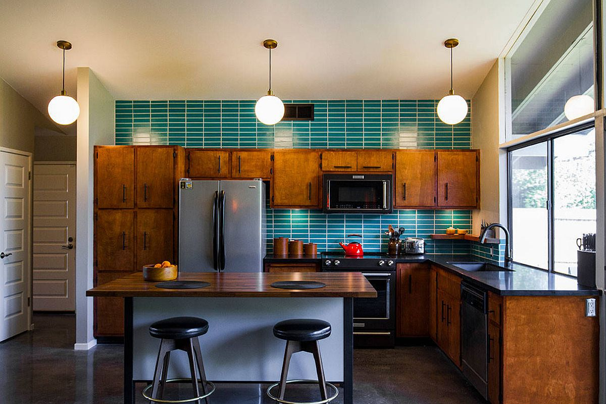 Exquisite mid-century kitchen with wooden cabinets, green tiled backsplash and and black appliances