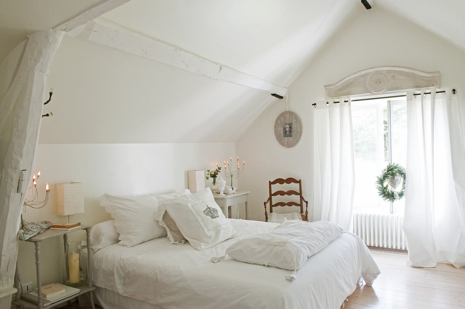 French counry style and a sense of delicate sophistication fill this light-filled, white attic bedroom