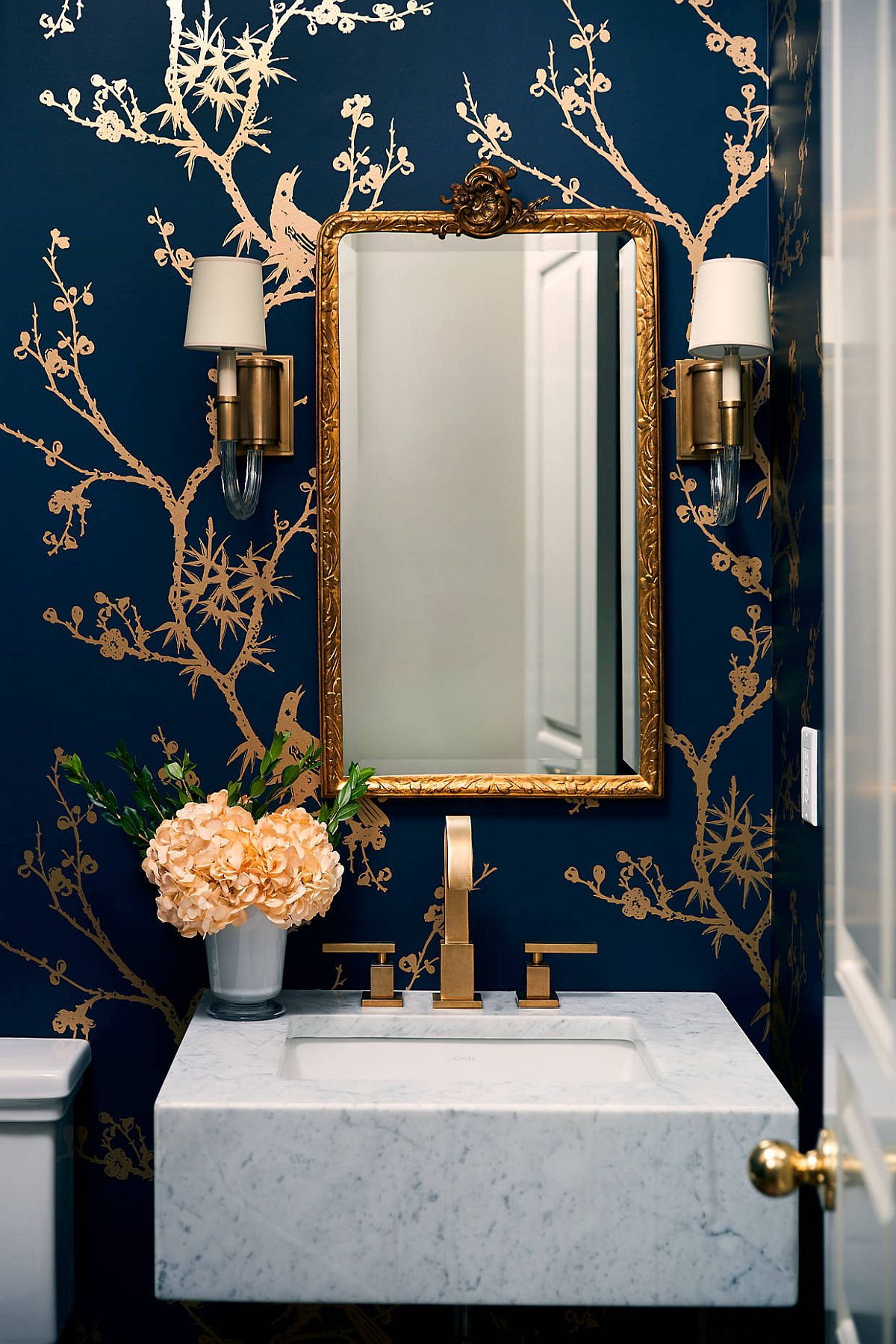 Glamarous blend of gold and dark blue in the contemporary powder room with white vanity