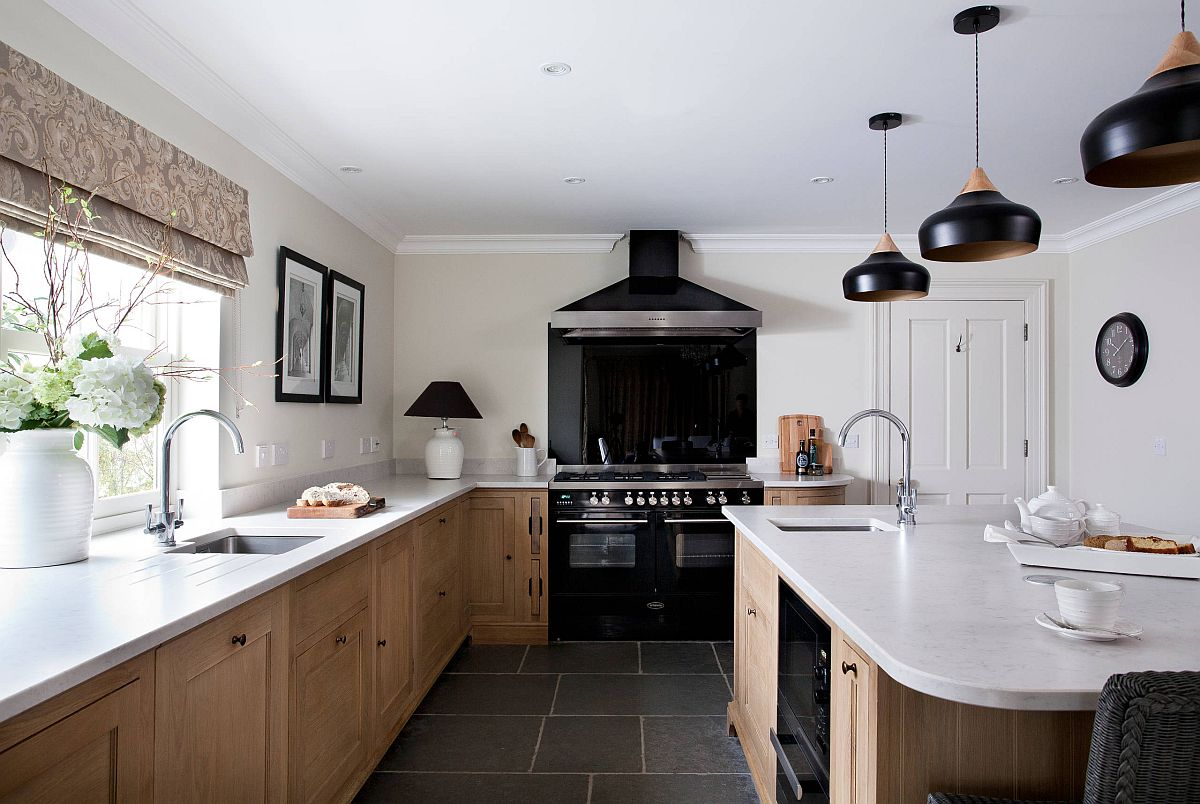 Gorgeous pendants in black accentuate the beuaty of the kitchen range in the same color