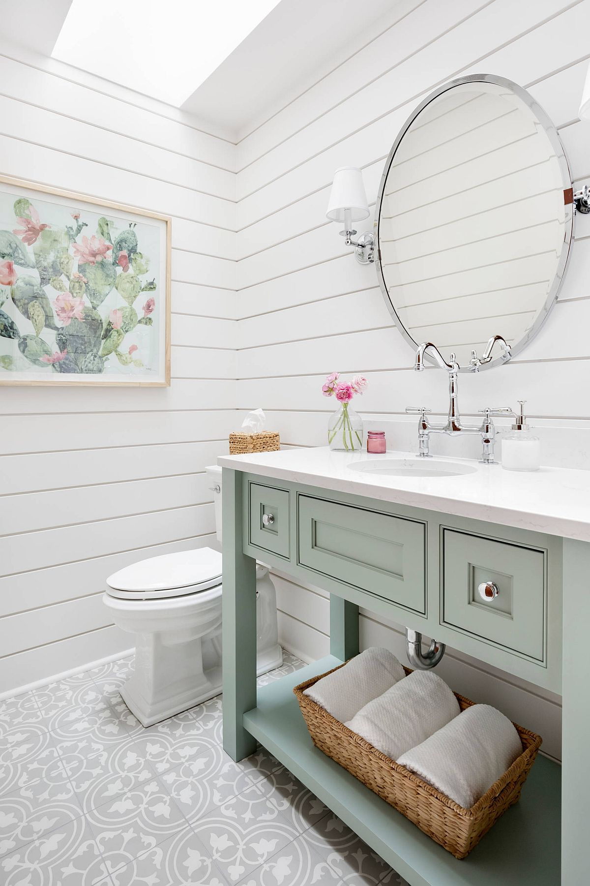 Gorgeous powder room in white with pastel green vanity and a skylight that brings in natural light