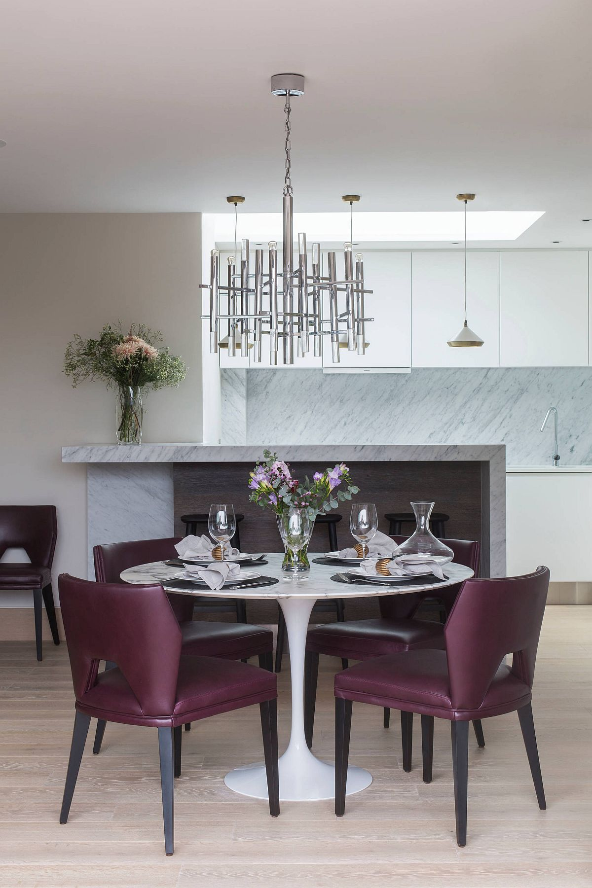 Gorgeous purple chairs coupled with white marble dining table with pedastal base