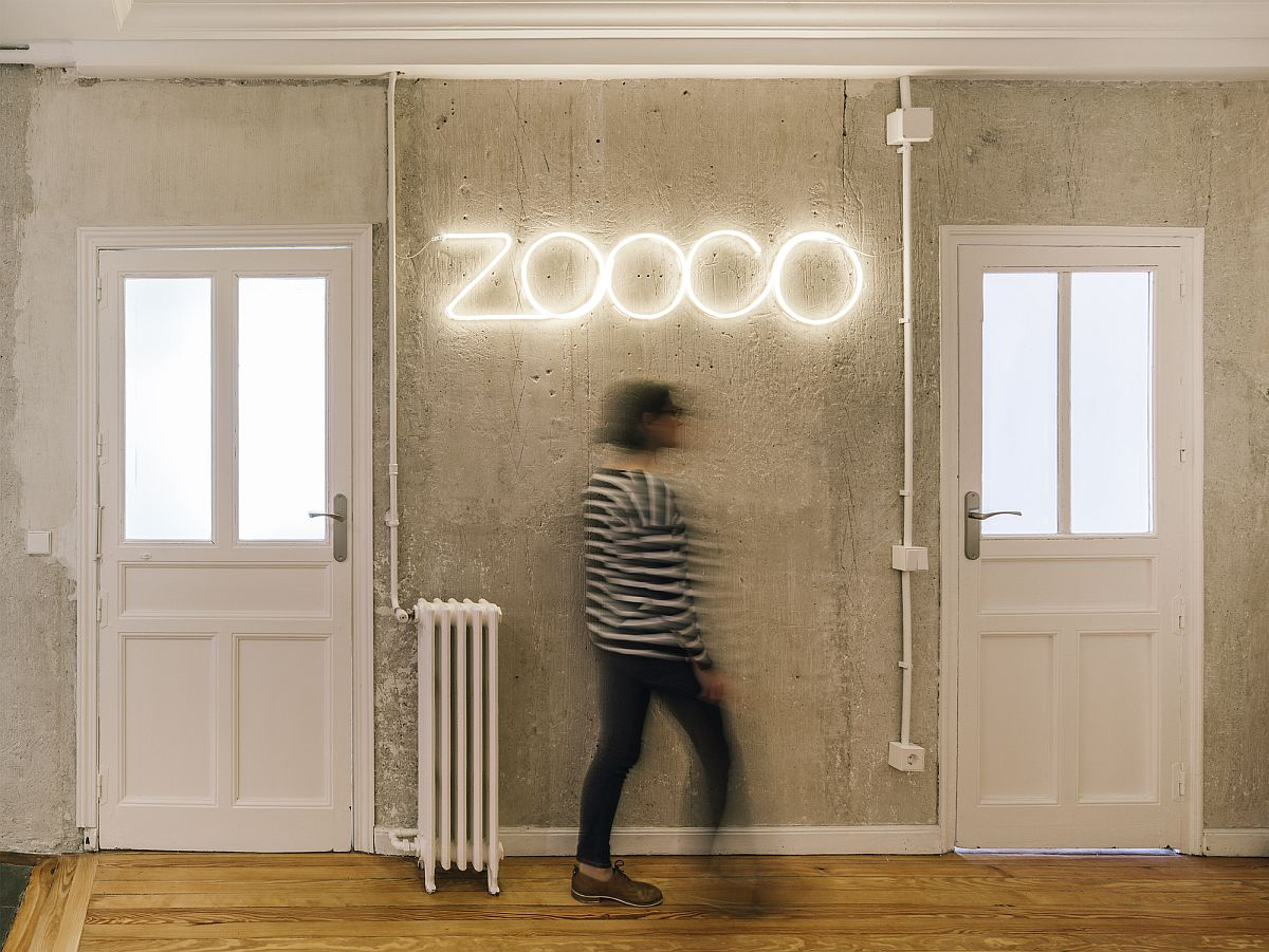 Illuminated light sign of the Studio on the wall with exposed concrete finish