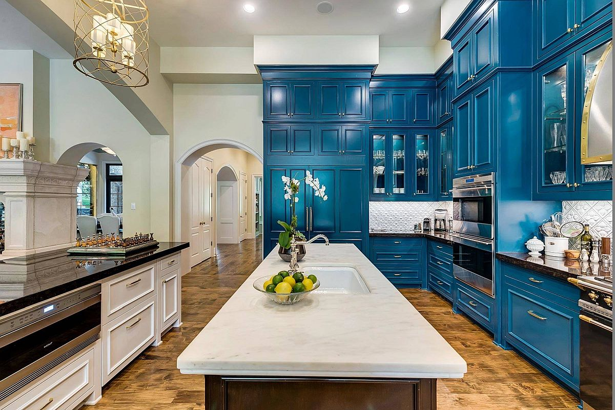 Lovely wood floor adds textural charm and pattern to the kitchen with blue cabinets