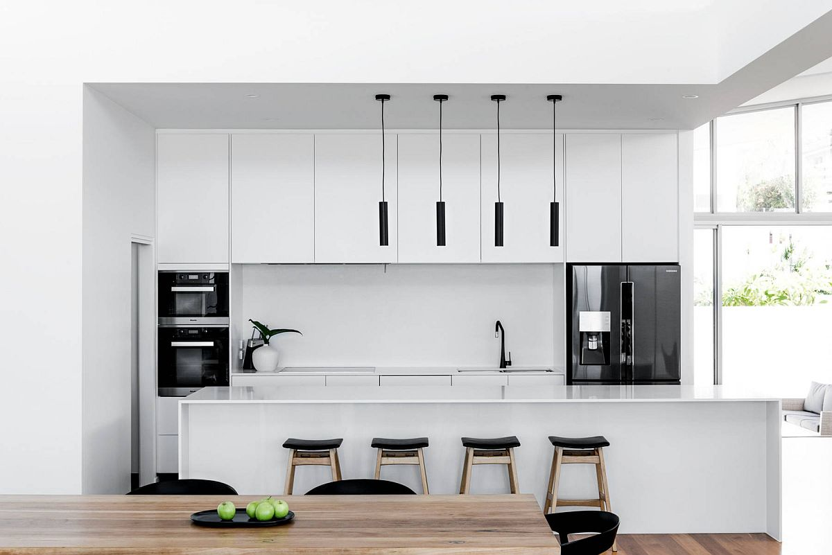 Minimal kitchen in white with equally smart dark appliances thrown into the mix