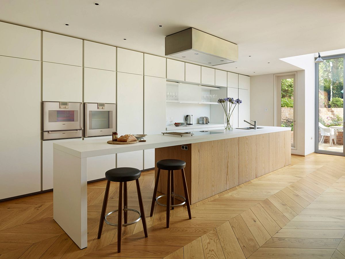Modern classic kitchen of London home with cozy wooden floor and white walls and cabinets