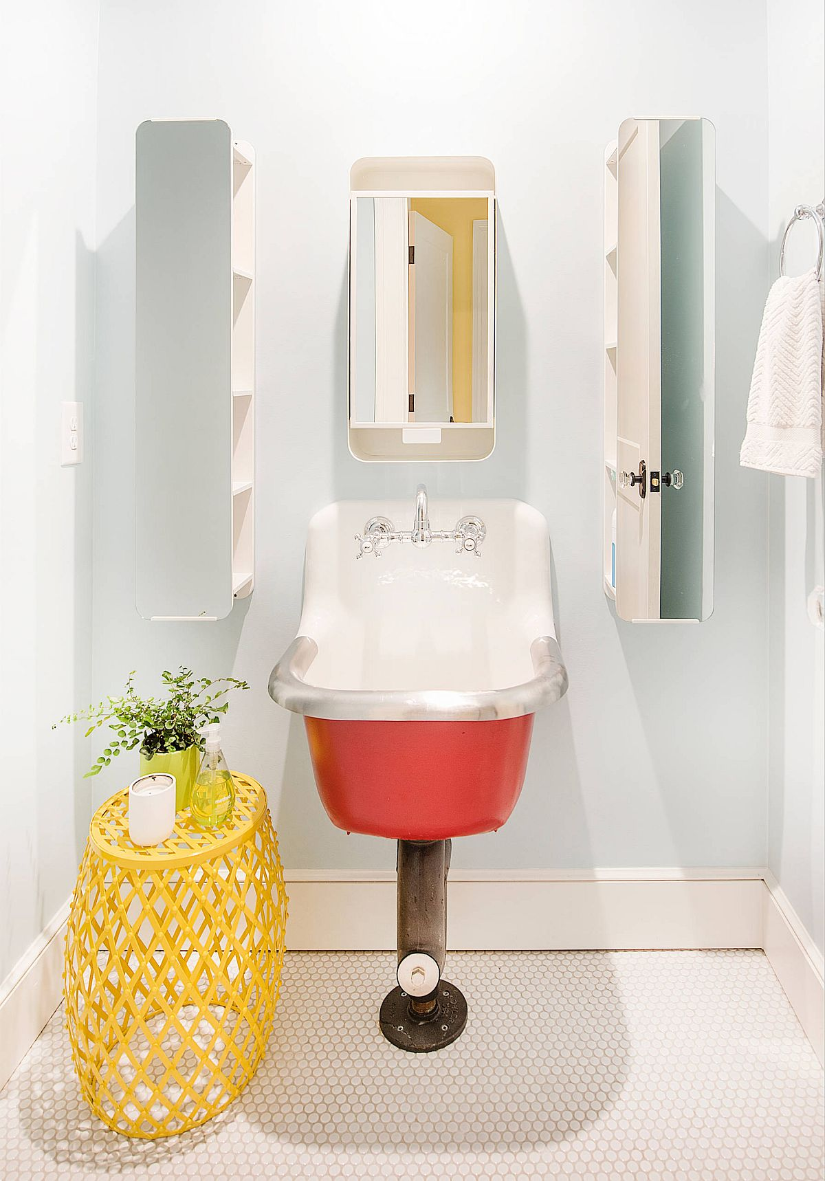 Modern farmhouse powder room with bright pops of pink and yellow, neutral backdrop and a unique sink