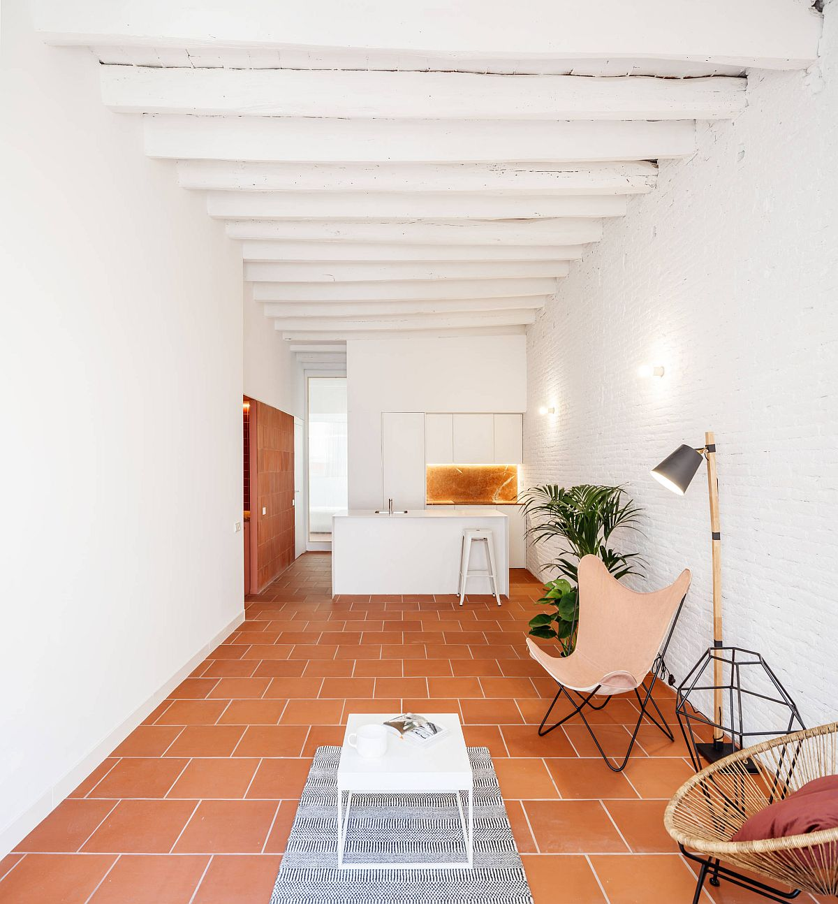 Modern living room of Barcelona apartment with white brick walls and terracotta tile floor
