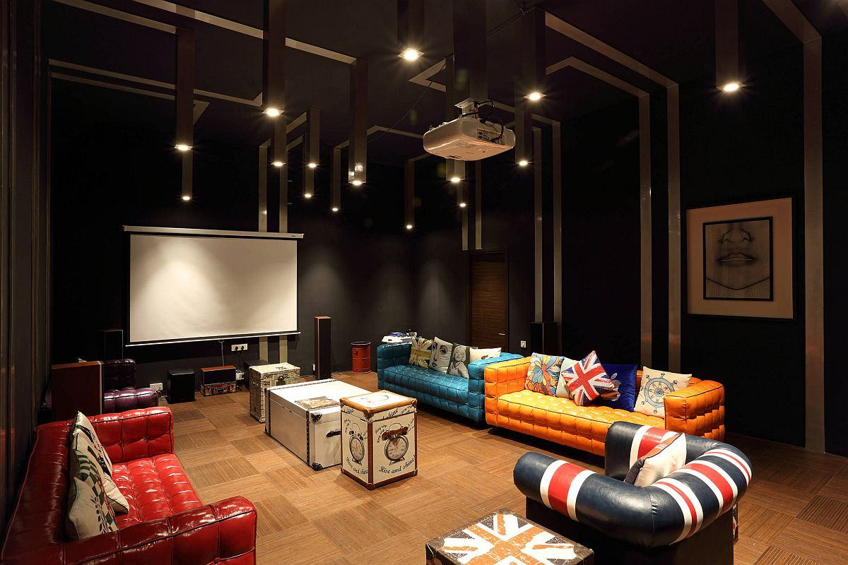 Multiple colored sofas in the home theater with vintage coffee tables and black walls all around