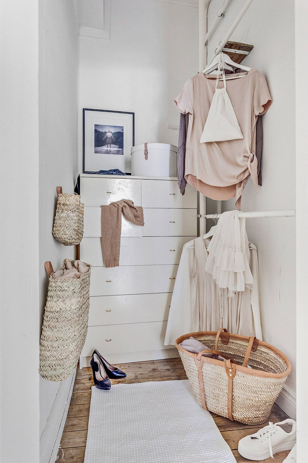 Neatly designed white cabinets and baskets create ample storage space in this wardrobe niche