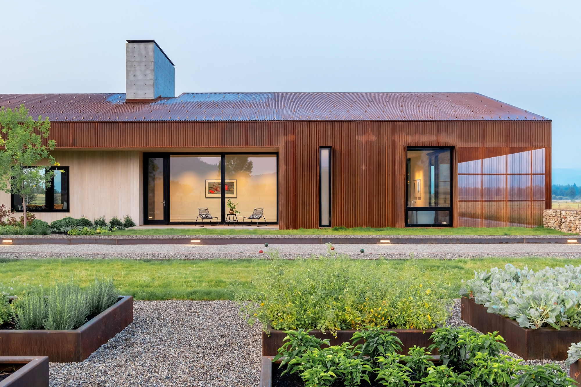 Oxidized-metal-wood-and-glass-shape-the-exterior-of-the-asymmetrical-Dogtrot-House-87002