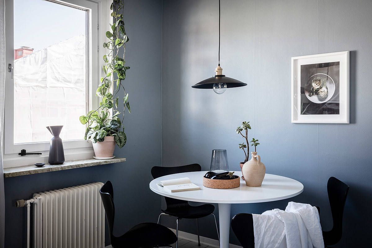 Pendant-and-chairs-add-black-to-the-small-Scandinavian-dining-space-with-blue-backdrop-73373