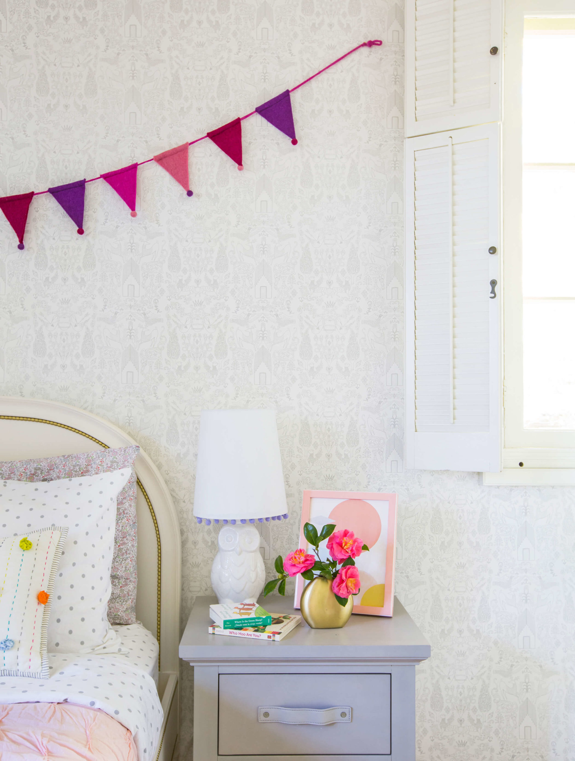 Playful girls' bedroom with subtle wallpaper