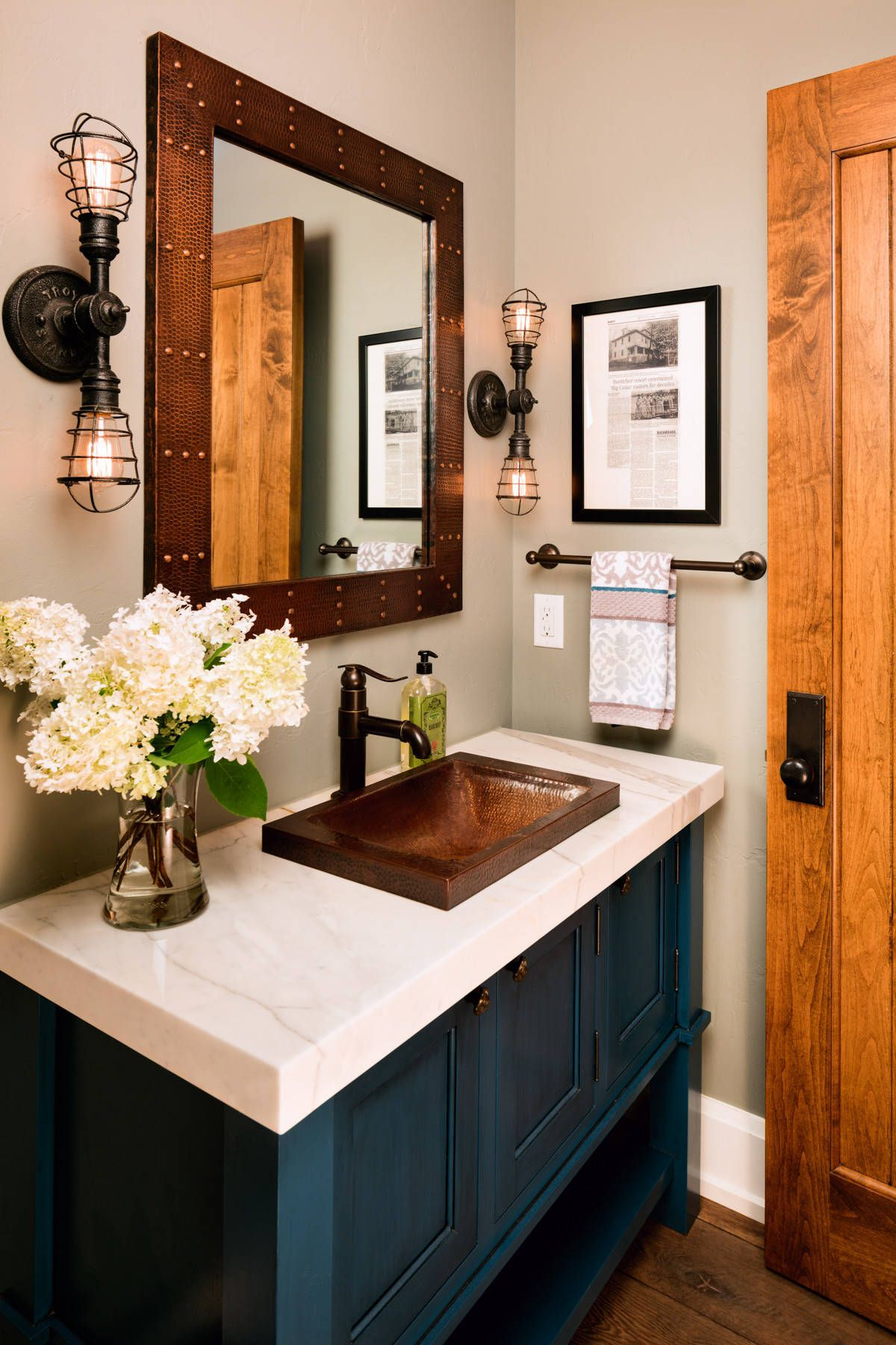 Posh vanity in blue along with sconce lighting for the farmhouse style powder room