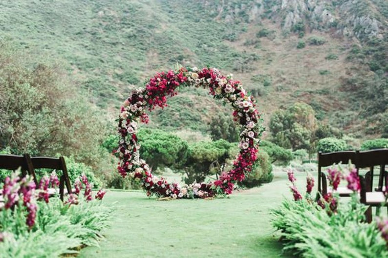 Round wedding arch covered in flowers