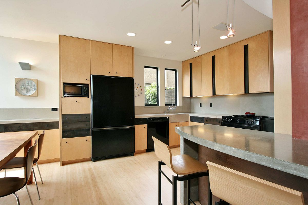 Simple and elegant L-shaped midcentury modern kitchen with wooden cabinets and black appliances