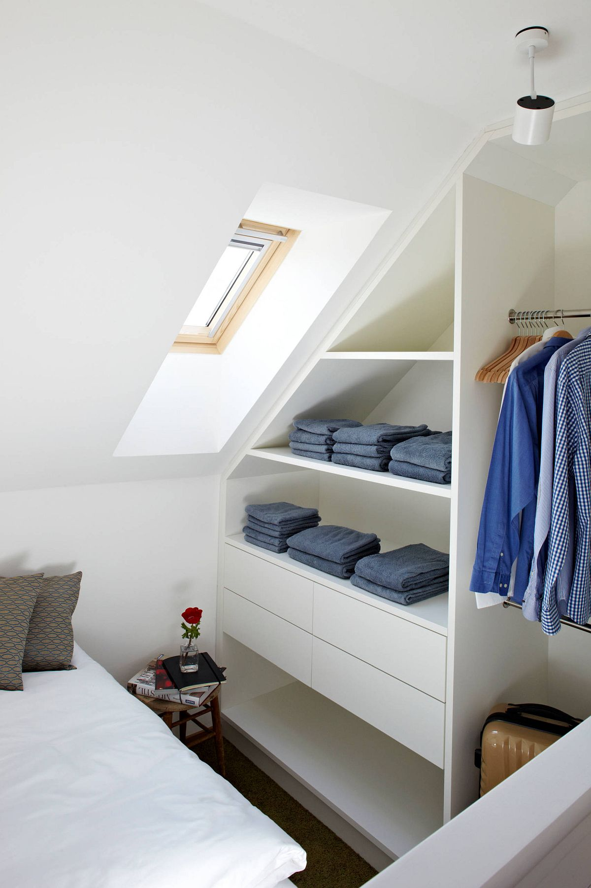 Small attic bedroom closet with neatly folded clothes and lots of shelf space