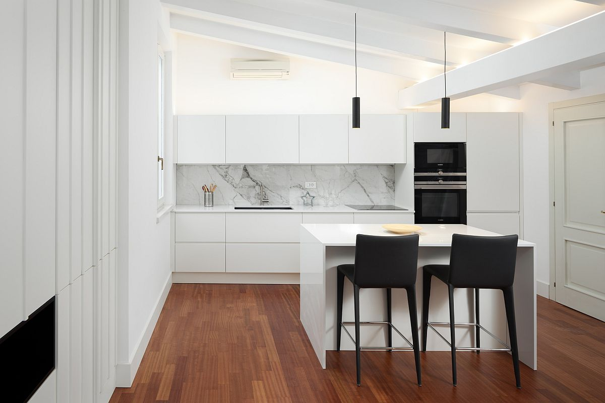 Sophisticated minimal kitchen in white where bar chairs and appliances usher in a dash of black