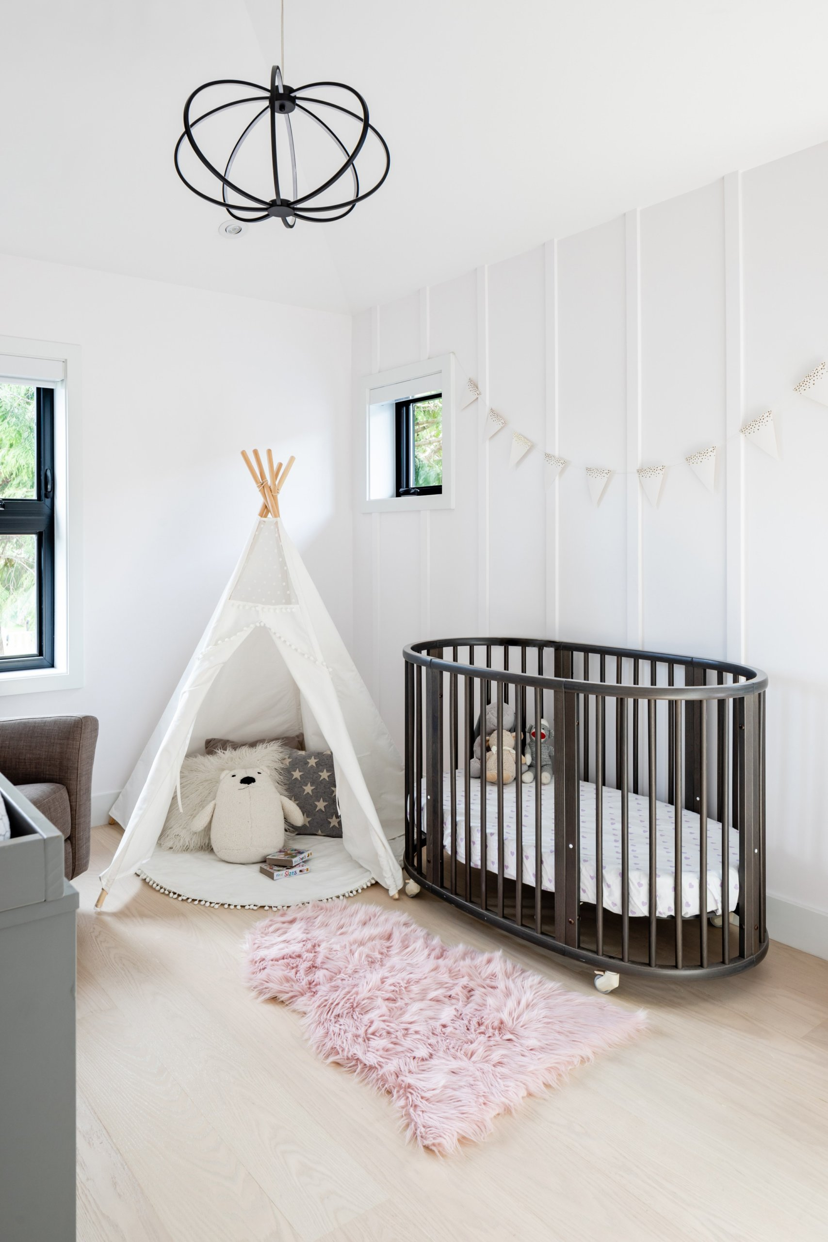 Stylish shabby chic girls' nursery with Scandinavian style and ample natural light